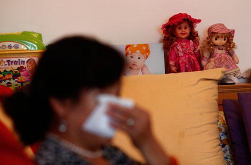 Hu, người mất cả gia đình con trai trên chuyến bay MH370, lau nước mắt trong cuộc phỏng vấn. Ảnh: Reuters