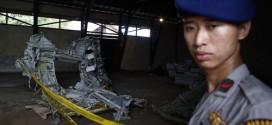 Cảnh sát đứng gác gần một mảnh vỡ thân phi cơ AirAsia gặp nạn tại kho ở cảng Kumai, Pangkalan Bun