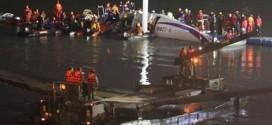 Lực lượng cứu hộ vây quanh máy bay trên sông khi trời tối dần.