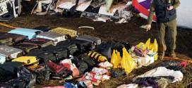 Một sĩ quan quân đội kiểm tra các hành lý và vật dụng thu thập được tại hiện trường tai nạn.