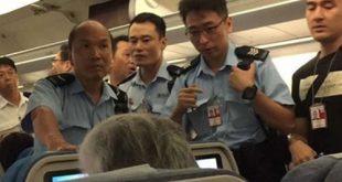 Cảnh sát lên máy bay khi nó vừa hạ cánh xuống sân bay Hong Kong.